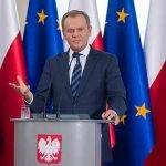 Donald Tusk na tle flag polskiej i unijnej